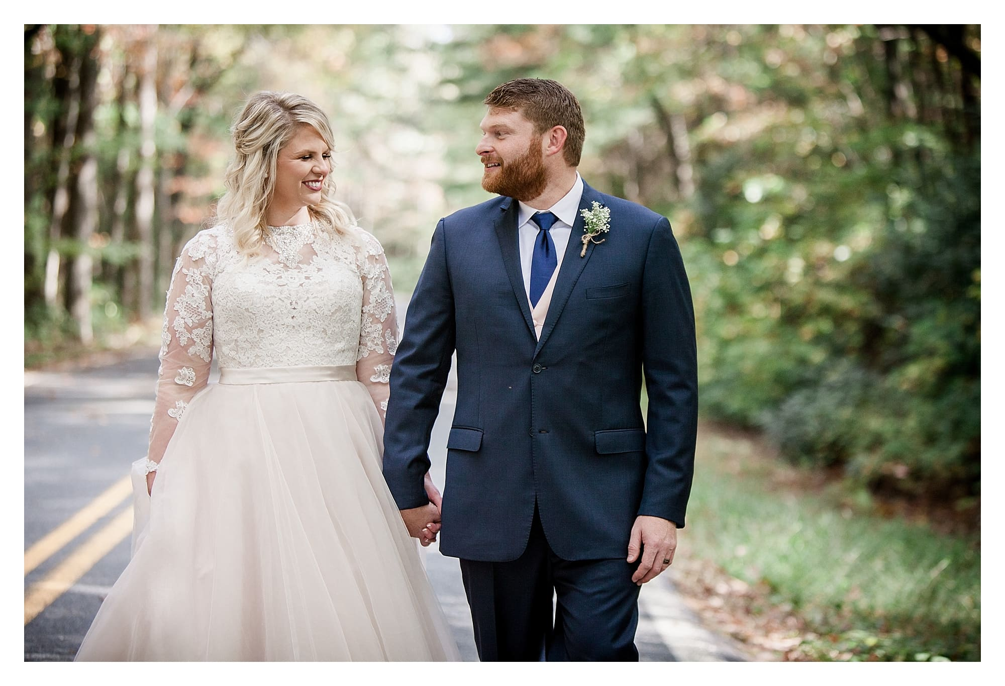 Bride and groom in road with fall foliage