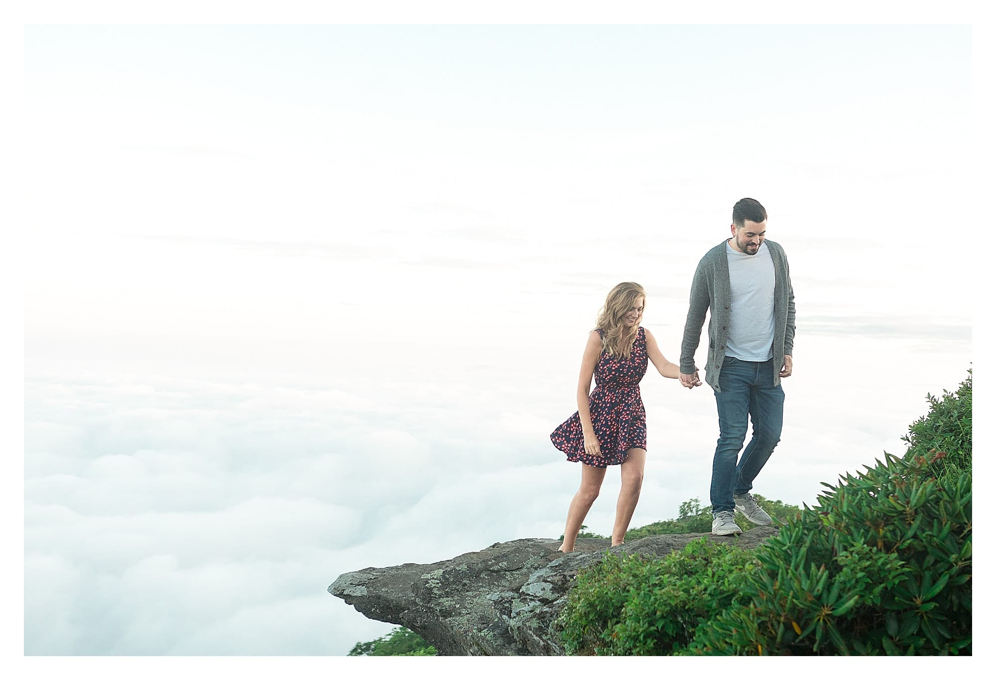 Engaged couple holding hands while walking on mountains edge