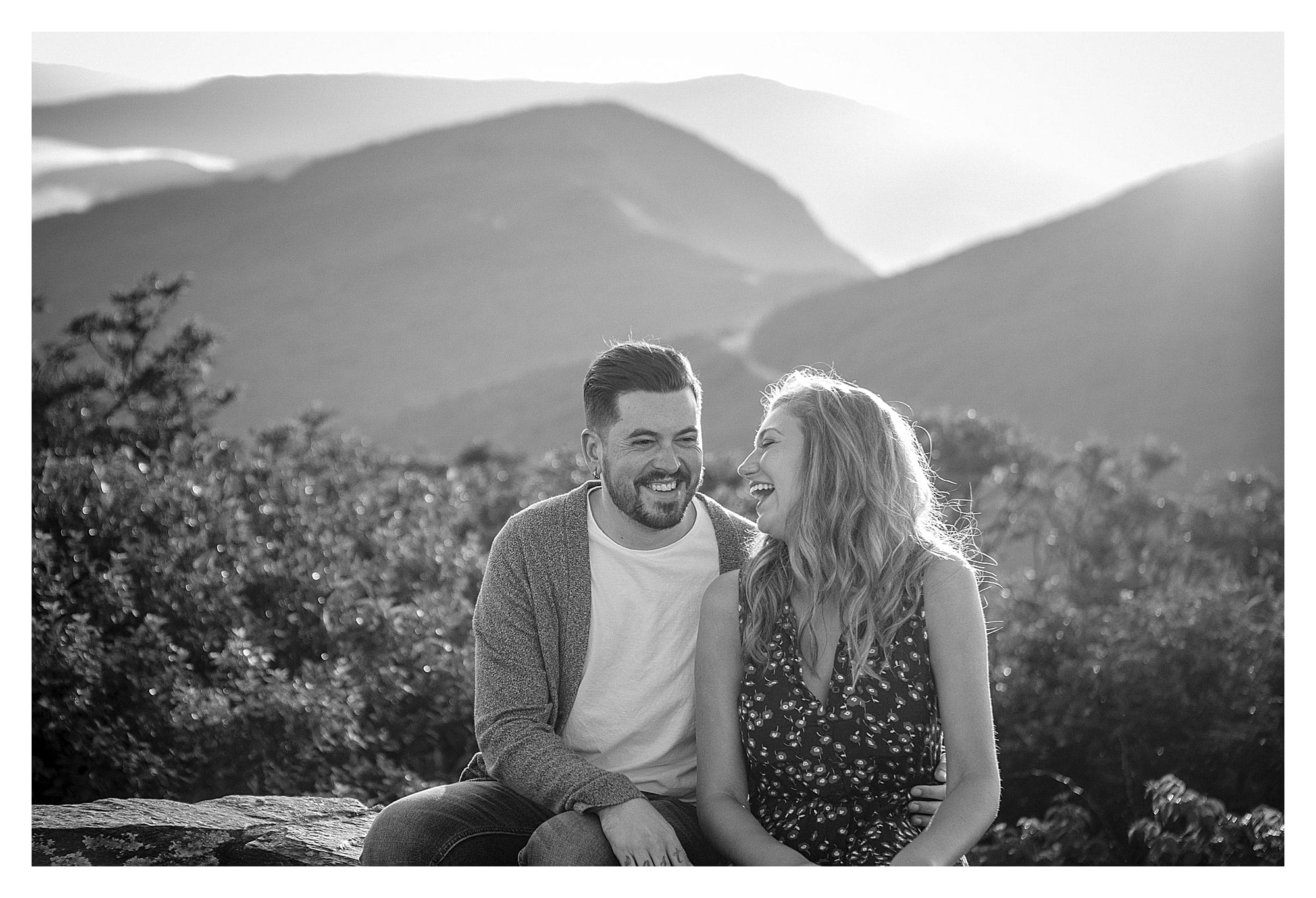 Black and white photo of engaged couple sitting and laughing with mountains behing them