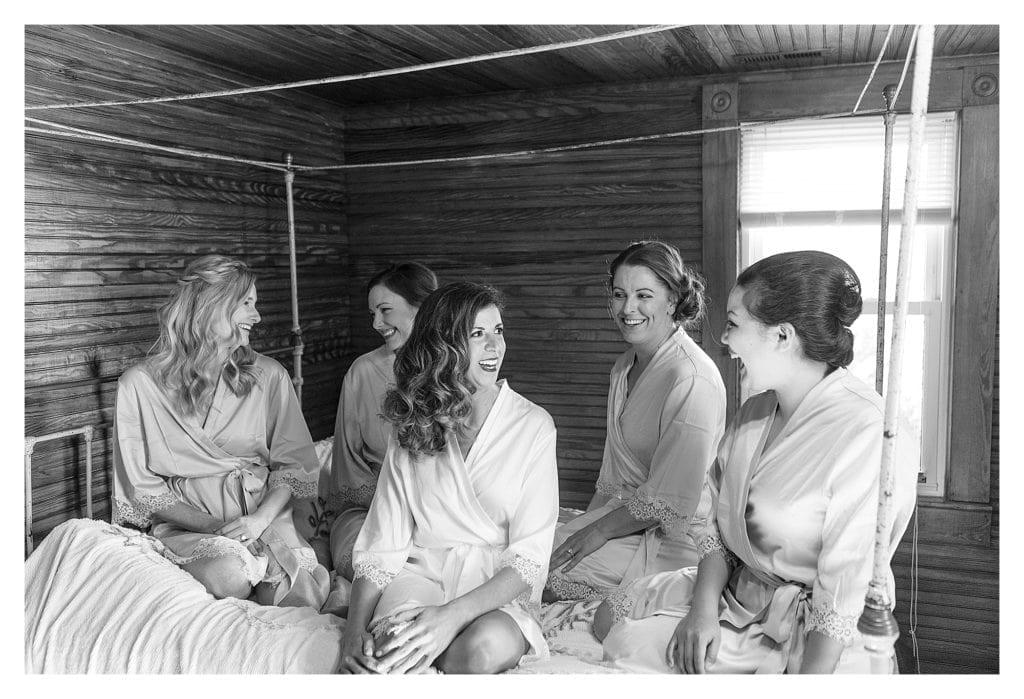 black and white image of bride and bridesmaids sitting on bed laughing while getting ready for wedding - kathy beaver photography