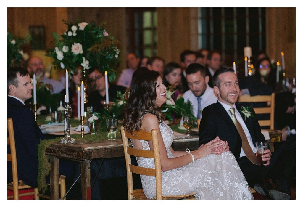 Bride and groom laughing while sitting holding hands and listening to wedding speeches - kathy beaver photography