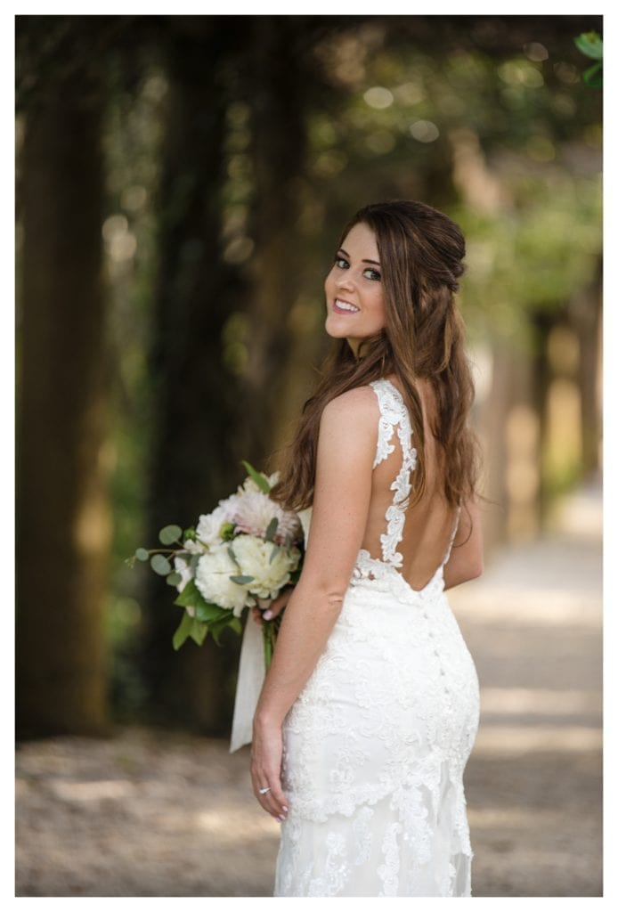 Close up of young bride smiling standing on treed pathway holding cream floral bouquet