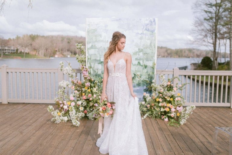 Bride holding bouquet down by side and looking down to the left standing in front of white, green and blue painted canvas backdrop on deck over looking a lake