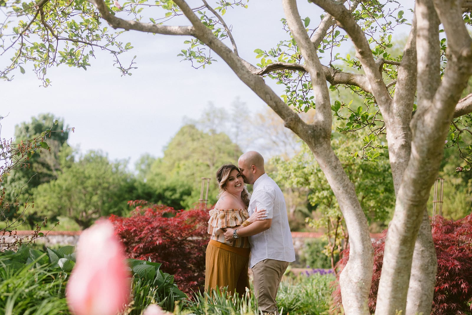 Newly engaged couple hugging one another laughing while standing outside on garden path