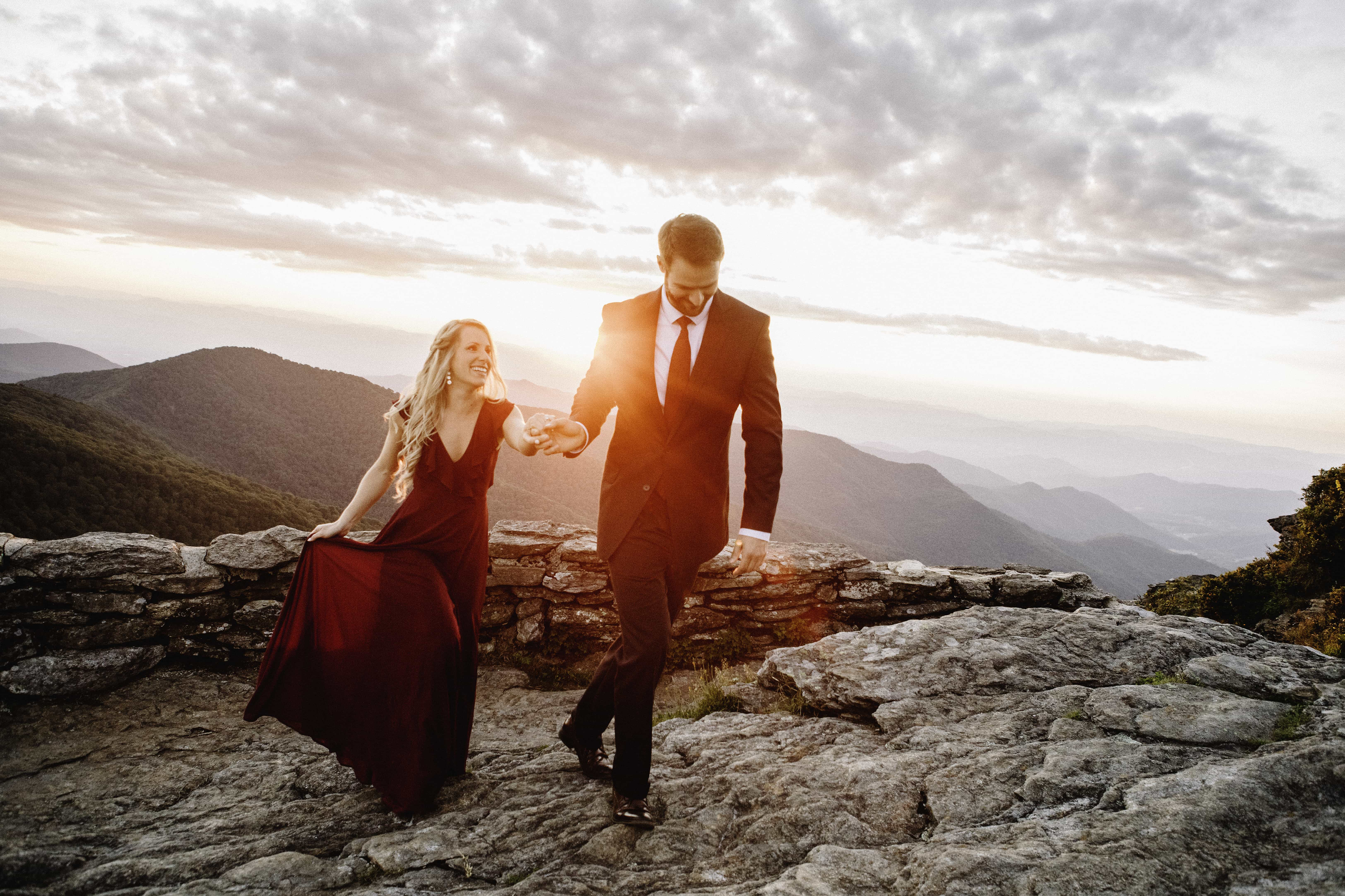 Man in suit holding fiances hand walking along rocky mountain side with mountain range in background at sunset