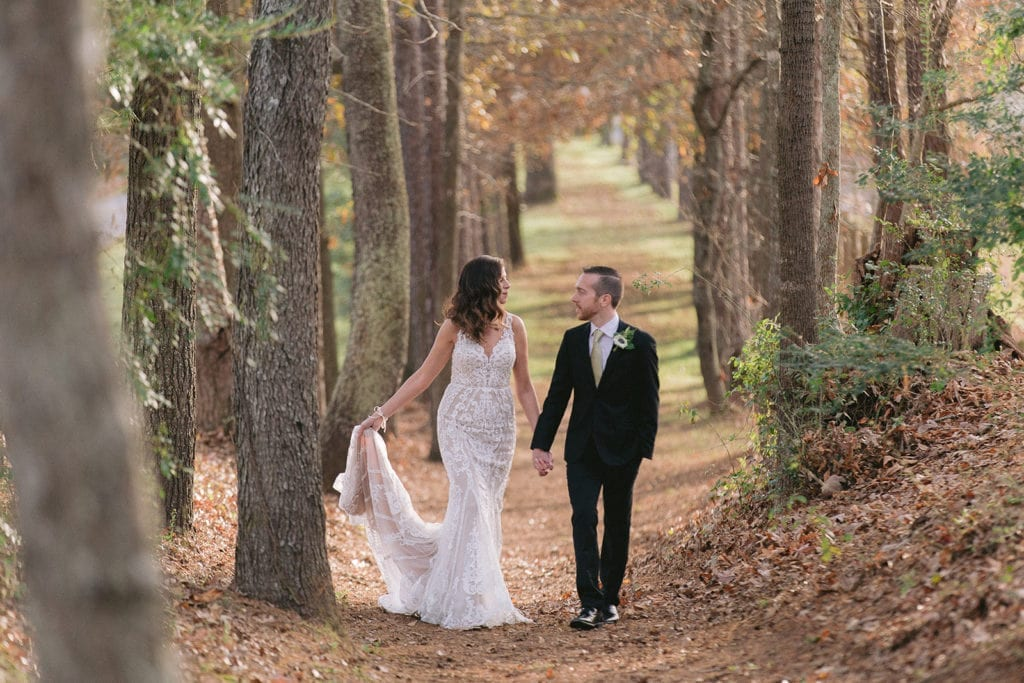 Fall wedding with bride and groom walking down path of trees.