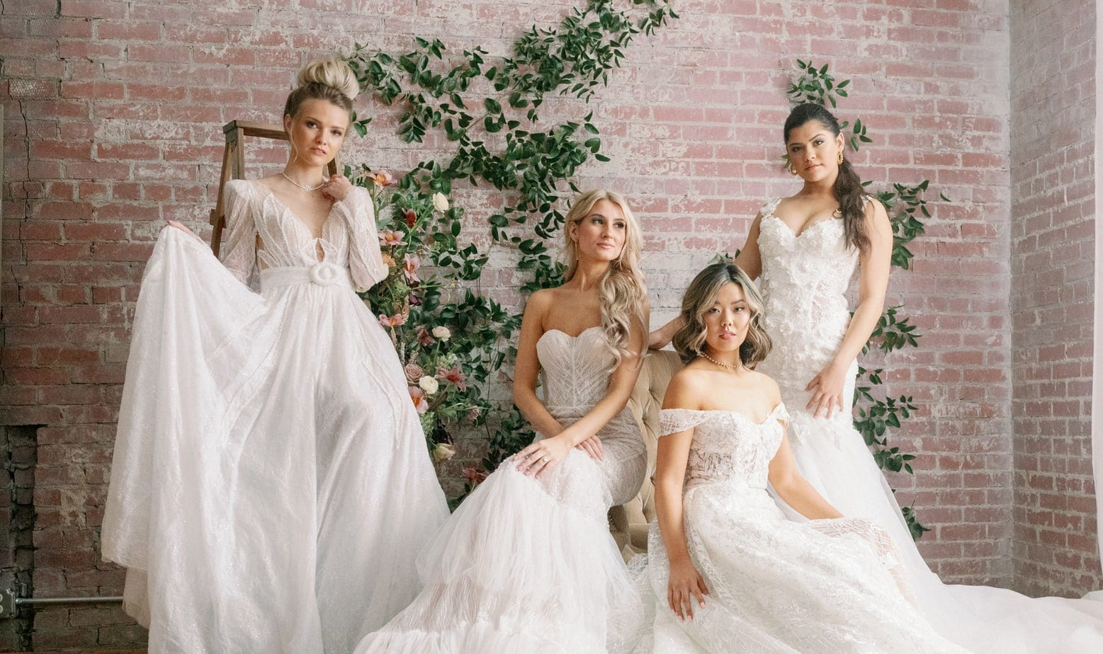 Four women wearing white vintage lace wedding gowns posing in front of light red brick wall with floral greenery running up it