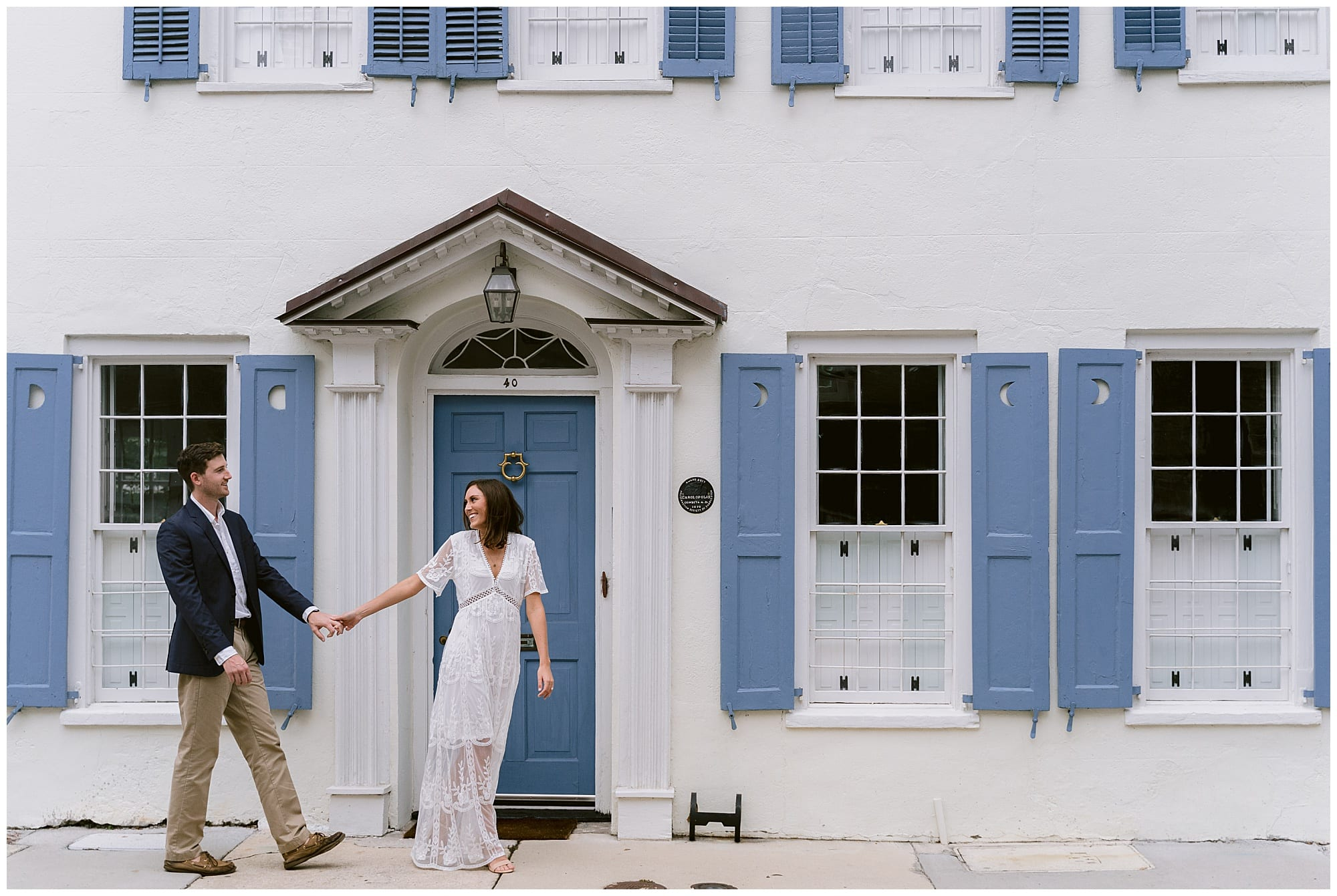 young engaged couple walking holding hands infront of white home with blue shutters in downtown charleston