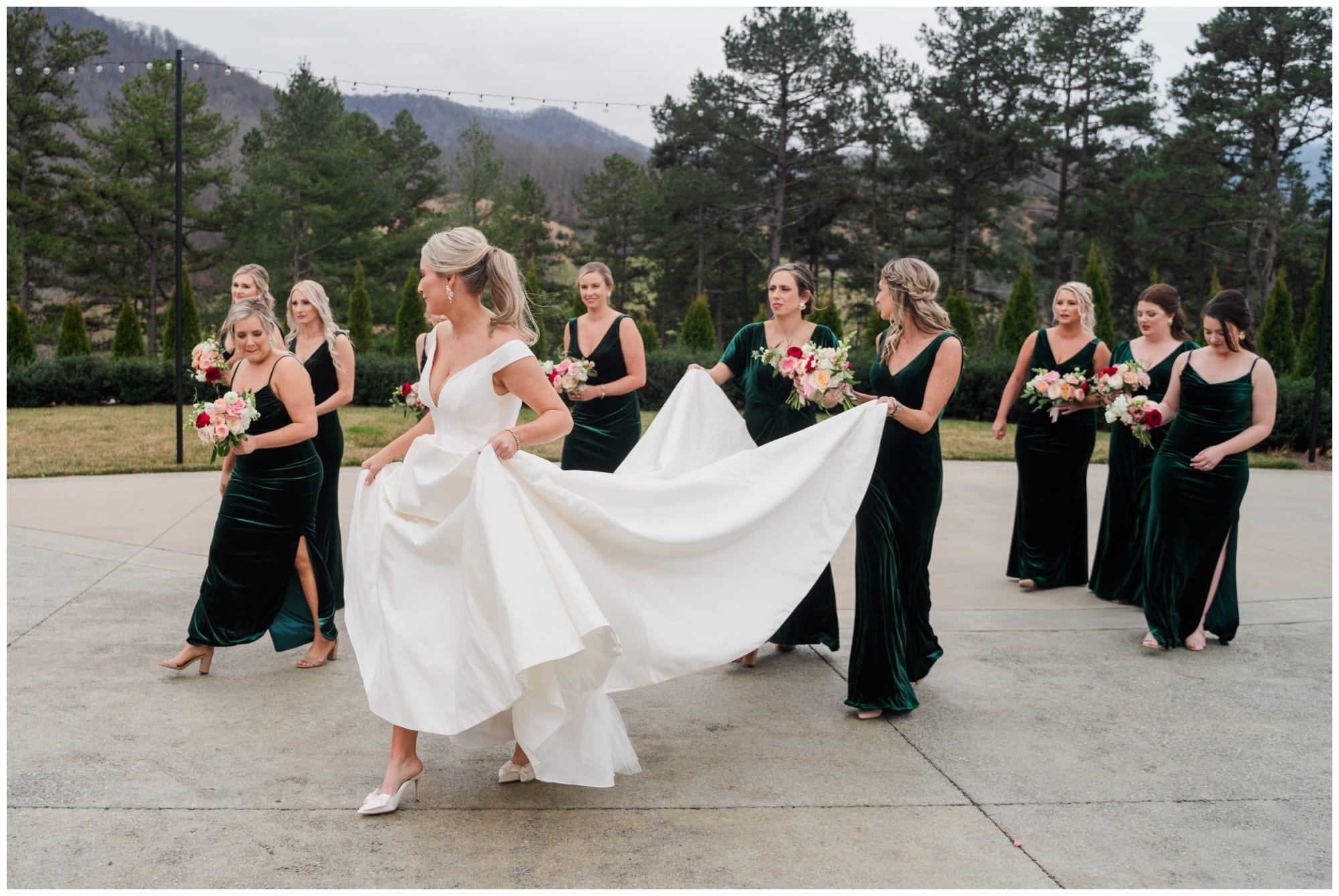 Bridesmaids carrying brides train at wedding
