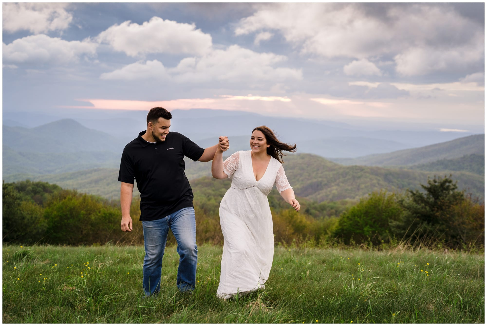 young engaged couple holding hands walking through grassy field overlooking mountain range smiling at one another