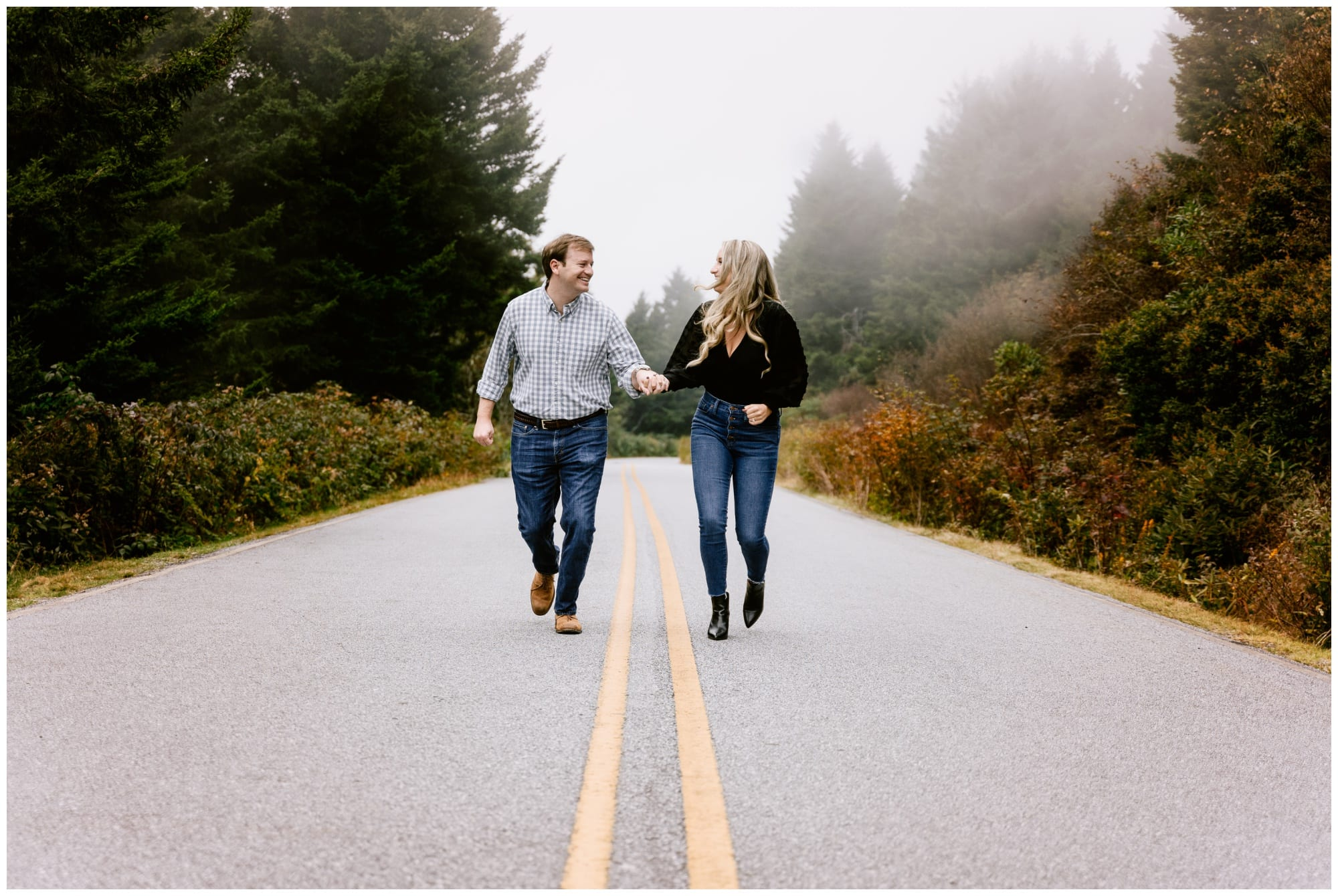 young engaged couple holding hands smiling at one another while running down the middle of a forested road for their outdoor winter engagement photo session