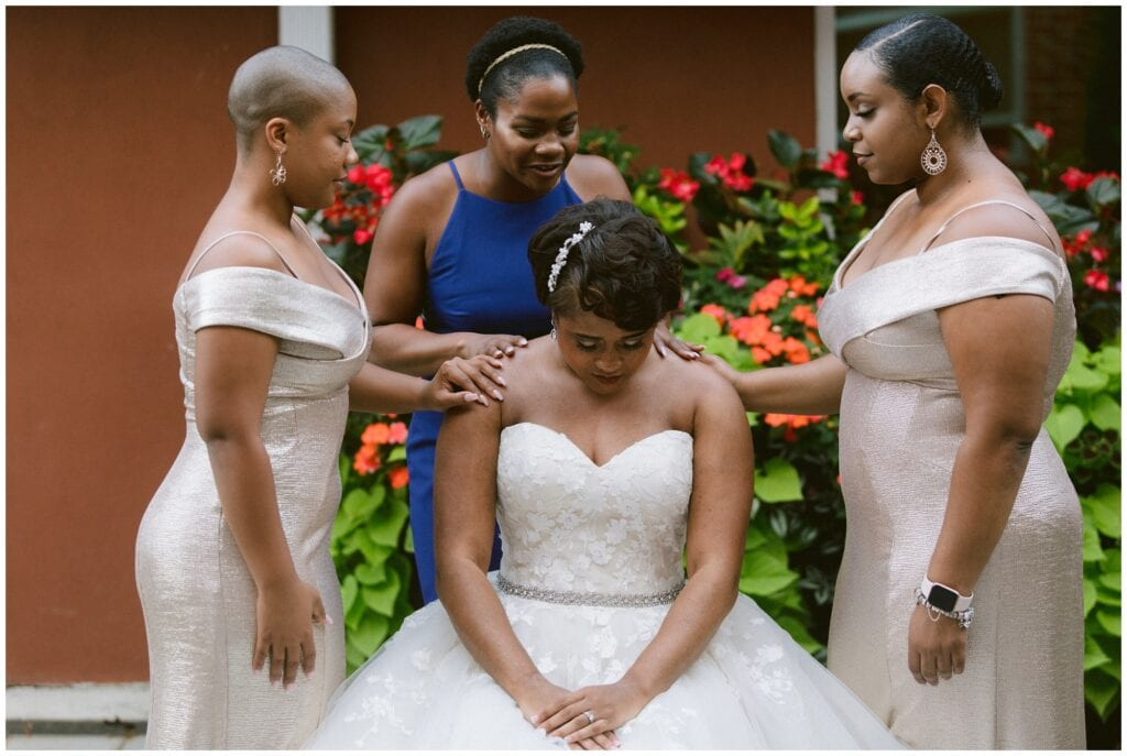 The bride and her bridesmaids praying together before their wedding ceremony.