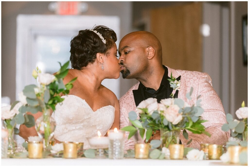 The bride and groom share a kiss at their table during their intimate dinner party wedding.